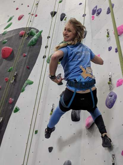 Emily climbing with Flat Stanley inside the new Whetstone climbing gym.