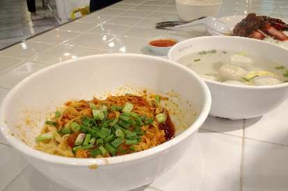 A noodle dish with a spicy sauce and green onions, meatballs in broth and barbecue pork over rice.
