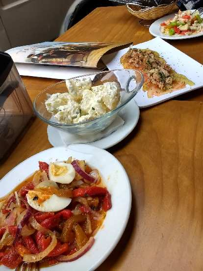 Tapas in Granada, including an egg, onion, and bell peppers dish; potato salad; shredded meat on sliced tomatoes; and shrimp with bell peppers and other sorts of vegetables.