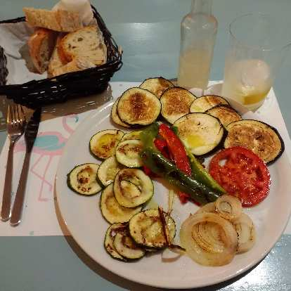 Bread and vegetables (cucumbers, onions, and tomatoes) grilled in olive oil and garlic in a nice restaurant in Nueva, Spain.