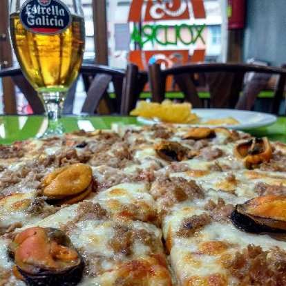 Pizza and Estrella Galicia beer at Xoldra Pizzeria in Melide, Spain.