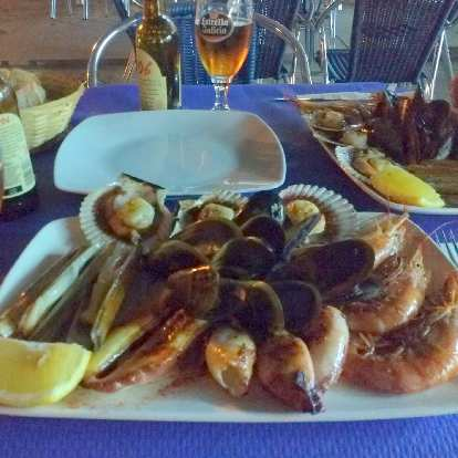 A seafood tasting menu, including grilled octopus, grilled squids, grilled pocket knife clams, big shrimps, scallops, and mussels in Fisterra, Spain.
