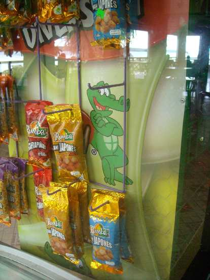 Happy lizard guy by packages of fried chips.