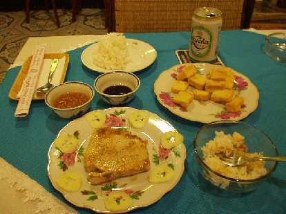 Grilled fish, steamed rice, fried tofu, and Huda beer in Hue.