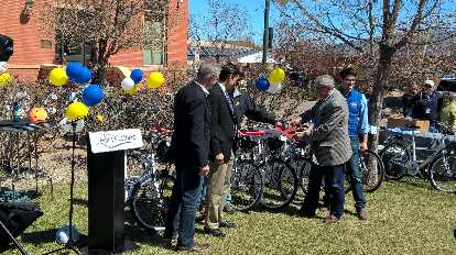 Mayor Wade Troxell cuts a ribbon at the grand unveiling of the Fort Collins Bike Share program.