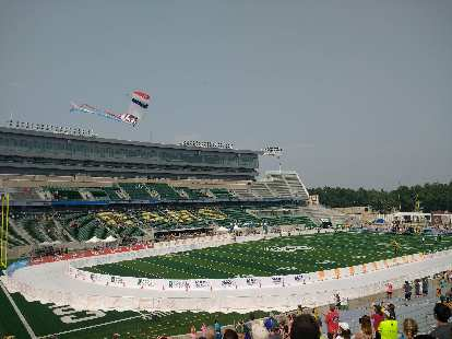 A skydiver bringing in the American flag to the stadium in the post-race activities.