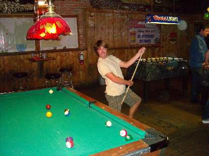 Derek doing something with a cue stick.