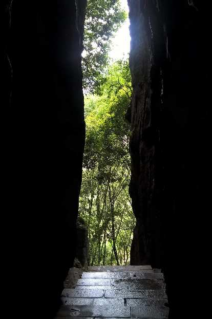 View of trees through an opening between stone walls at the Fujian Linyin Stone Forest.