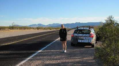 [Mile 324, 7:54 a.m.] Raquel and the Asiatic Wildcat crew vehicle await as I exit Death Valley National Park.