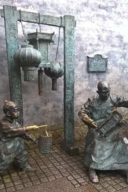 Statues of two Chinese people, one carrying a lantern and another some sort of musical instrument in Fuzhou, China.