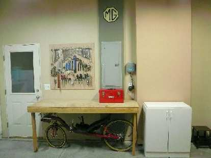 [After]  The front of the garage with pegboard, tools, and relocated cabinet.  Note that the recumbent now has a space all to herself -- under the workbench!