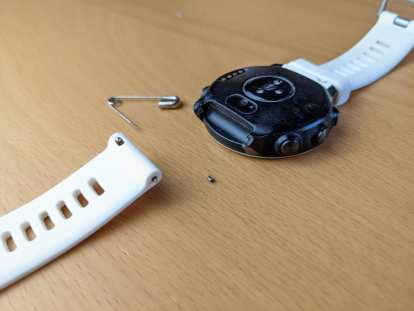 The Garmin Forerunner 645 Music watch with a broken watch pin support, the new watch pin collar I made, and the white watchband.