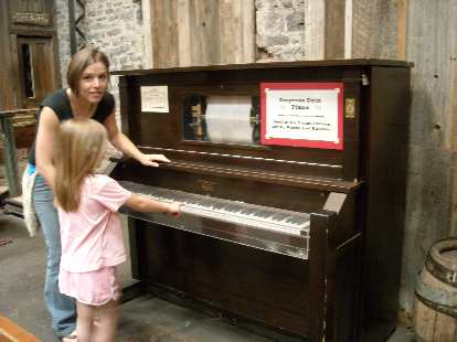 Leah and Faith with a functional player piano at the Ghost Town Museum.