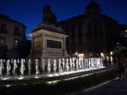 Fountain and statue at the Plaza de Isabel La Católica in Granada, Spain at night.