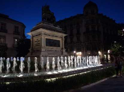 Fountain and statue at the Plaza de Isabel La Católica in Granada, Spain at night.