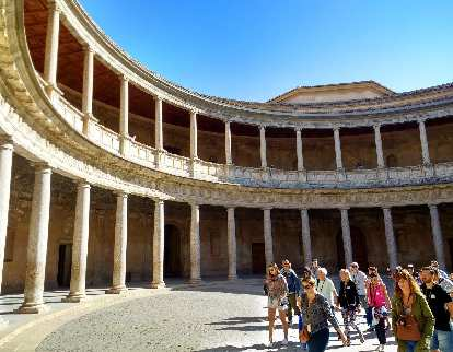 Visitors in the center of the lower level of the circular patio of the Palace of Charles V (Palacio Carlos V).