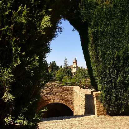 View of a building through manicured shrubs at Generalife.