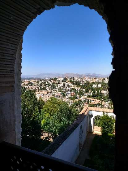 The view of Granada through a stone archway at Generalife.