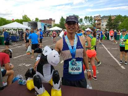 Felix Wong with a chocolate milk cow after the 2017 Grandma's Marathon.