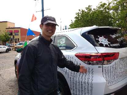Felix Wong with a Toyota Highlander wrapped with the list of all participants' names in the 2017 Grandma's Marathon.