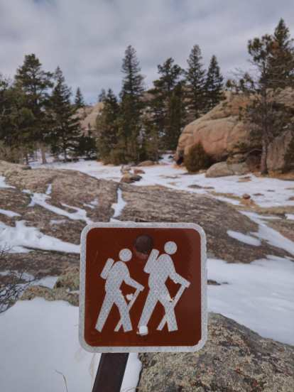 sign depicting two hikers, snow on rocky ground, evergreen trees