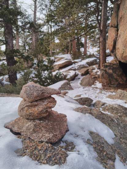 a cairn and evergreen trees