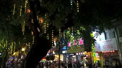 Strips of lights dangling off trees on the pedestrian shopping street of Lianxin Rd. in Guangzhou, China.