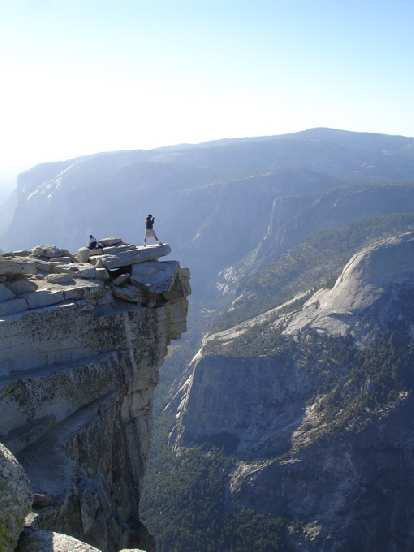 "On the ""diving board"" just across from the top of Half Dome was a young couple shooting photos and taking in the view."