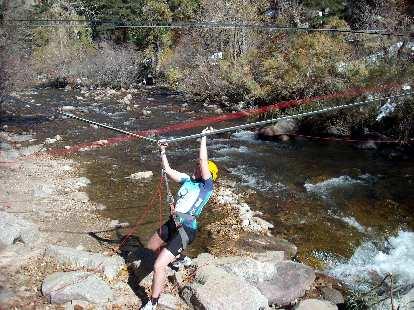 Kelly zip-lining across a creek.