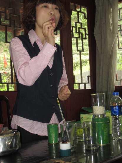 A Longjing tea plantation representative giving a sales pitch on the benefits of Longjing tea.