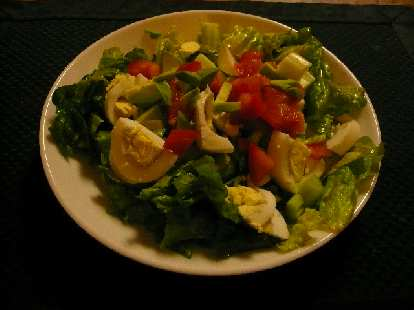 Chef salad with green lettuce, hard-boiled eggs, tomatoes, avocado, and celery.