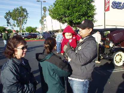 During the last weekend of 2003, I boarded a jet to spend some time with sweet Sharon and her wonderful family.  Here's Mary Jane, Karen, little Emmalee, and Allen awaiting the start of the annual Holiday Motor Excursion in Pasadena.