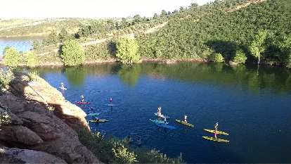 Yogis on paddleboards paddling back to Satanka Cove at Horsetooth Reservoir.