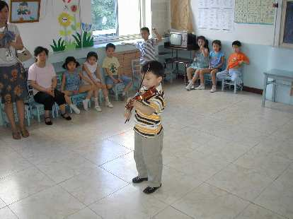 A kindergarten class with a boy playing the violin.