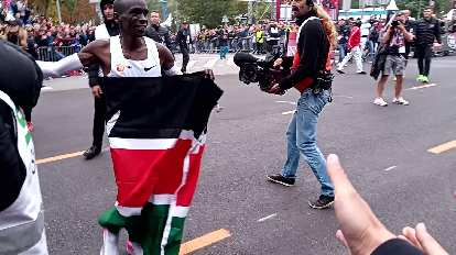 After finishing, Kipchoge ran around with the Kenyan flag. He missed slapping my outstretched hand in this photo.