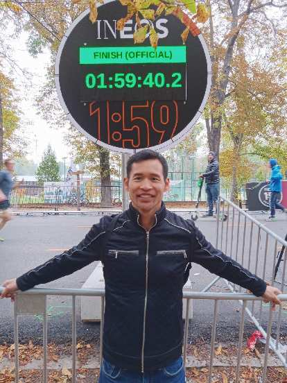 Felix Wong in front of a time clock displaying Eliud Kipchoge's time of 1:59:40. Nowadays I am happy to run 15 miles in that time. Kipchoge ran a whole marathon!
