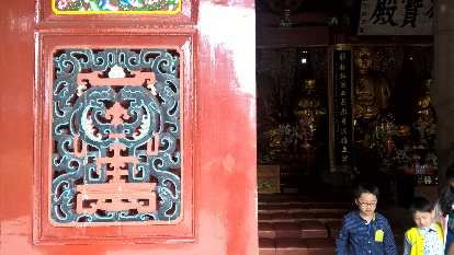 Red wall with exquisite carvings at the Kaiyuan Temple in Quanzhou, China.