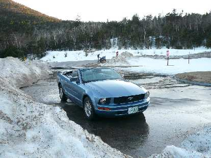 The Mustang takes a breather at a scenic overlook while a motorcyclist on a Suzuki GSX-R pulls up.