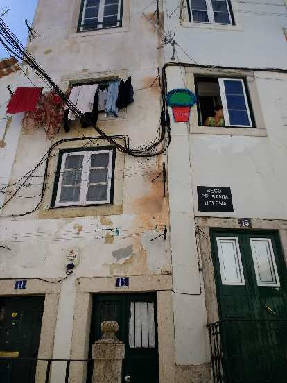 A woman peering out the window of a townhome in Alfama.