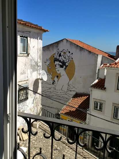 On the side of a building, a drawing of a woman in the sea with the sun behind and bird in front.