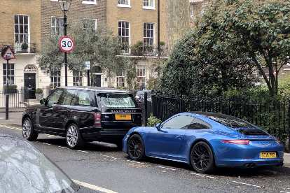 A black Land Rover Discovery and Blue Porsche 911 in a neighborhood north of Hyde Park.
