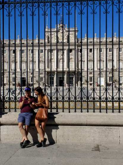 A man and woman looking at a smartphone in front of the Royal Palace of Madrid.