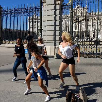 Folks practicing a choreographed dance in front of the Royal Palace of Madrid.