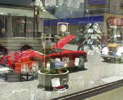 Reflection of a red MGA on the glass windows of a boutique store.