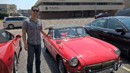 Felix Wong in front of Jennifer Orum's red 1970 MGB roadster.