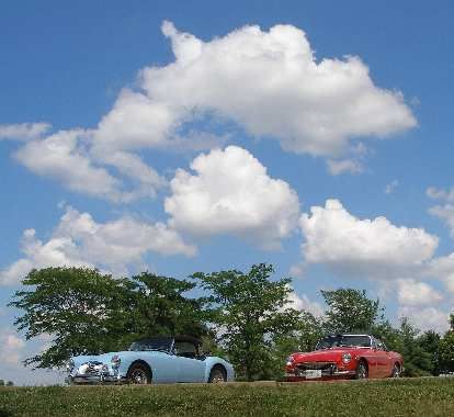 Mike Jacobsen's light blue MGA and Jennifer Orum's red 1970 MGB below some puffy clouds at the Wright City rest stop off I-70.