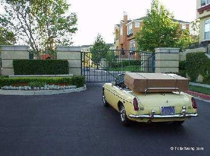 yellow MGB convertible, large cardboard box on luggage rack, bike box