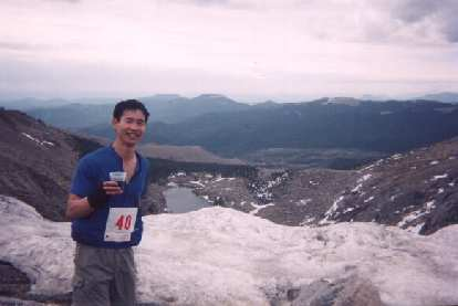 [Mile 6, 9:13 a.m.] Felix Wong takes a break to chat with Anne and enjoy a Coke.  It was still warm enough that his windbreaker and beanie hat were stashed in his pockets and arm warmers rolled down.