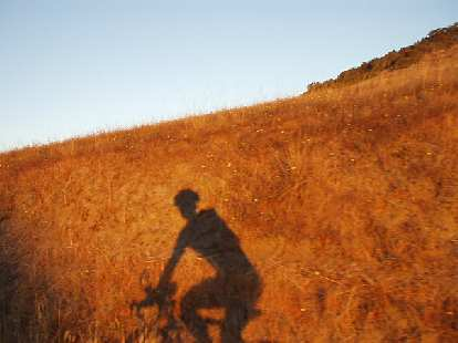 [Mile 24, 6:28 a.m.] This is me... or at least my shadow among the Marin hills made golden by a rising sun.