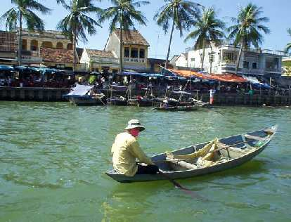 Man in canoe at harbor in Hoi An.